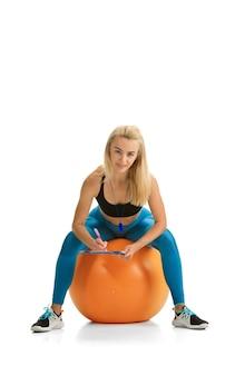 Mooie vrouwelijke fitnesscoach die geïsoleerd op een witte studiooppervlak oefent