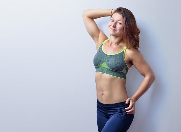 Mooie vrouwelijke fitnesstrainer in grijze top en zwarte legging is poseren, vooraanzicht, geïsoleerd op de witte achtergrond.