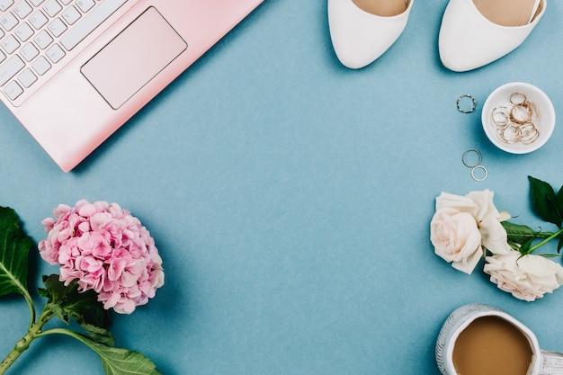 Mooie vrouwelijke flatlay van roze laptop en witte schoenen van de vrouw, jewerly en bloemen op blauwe, selectieve nadruk