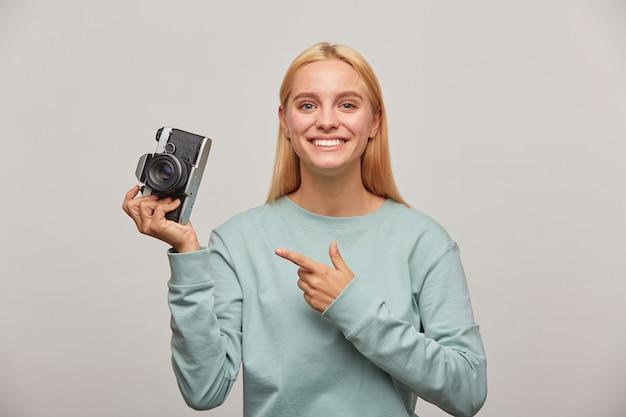 Mooie vrouwelijke fotograaf die een fotosessie maakt, geïnspireerd door de retro vintage fotocamera in de hand