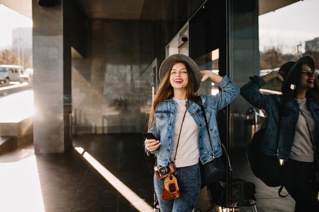 Mooie vrouwelijke fotograaf in trendy outfit met zwarte telefoon poseren glimlachend in de buurt van winkelcentrum.