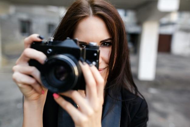 Mooie vrouwelijke fotograaf poseren met camera