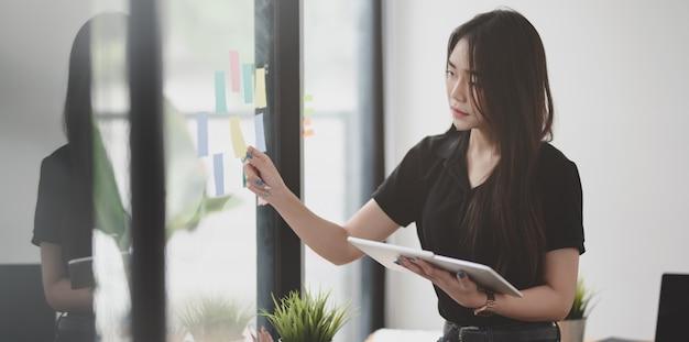Mooie vrouwelijke freelancer die het idee van kleverige nota's opneemt