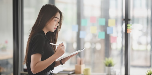 Mooie vrouwelijke freelancer die het idee van kleverige nota's verzamelt