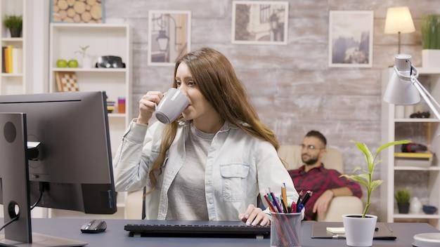 Mooie vrouwelijke freelancer die op de computer typt terwijl hij thuis werkt. vriend op de achtergrond kijkt tv.