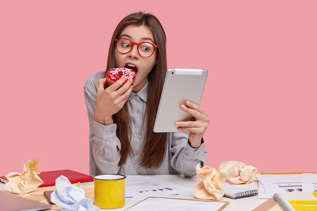 Mooie vrouwelijke freelancer heeft koffiepauze na het bestuderen van documentatie, houdt tablet vast, kijkt film online, bijt lekkere zelfgemaakte donut