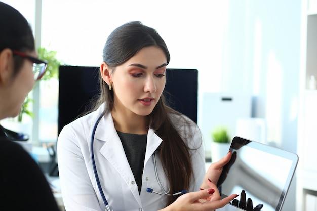 Mooie vrouwelijke geneeskunde arts uit te leggen