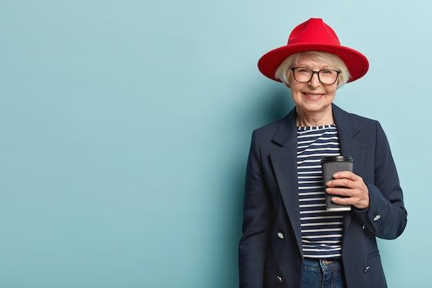 Mooie vrouwelijke gepensioneerde m / v heeft ontmoeting met collega, bespreekt iets tijdens koffiepauze, houdt papieren kopje cappuccino, draagt stijlvolle outfit, geïsoleerd op blauwe muur, kopie ruimte aan de linkerkant