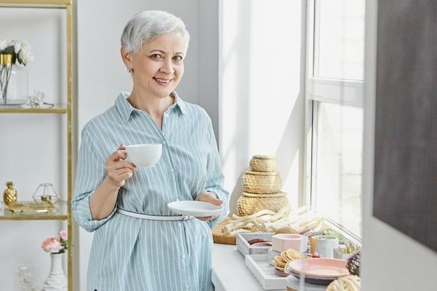Mooie vrouwelijke gepensioneerde m / v in gestreepte zomerjurk bedrijf schotel en mok, het drinken van thee, poseren in stijlvol interieur met eten en decoraties op de vensterbank. rijpe vrouw die van ontbijt geniet