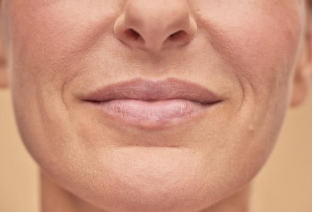 Mooie vrouwelijke gezichtsstudio die op een beige achtergrond is ontsproten