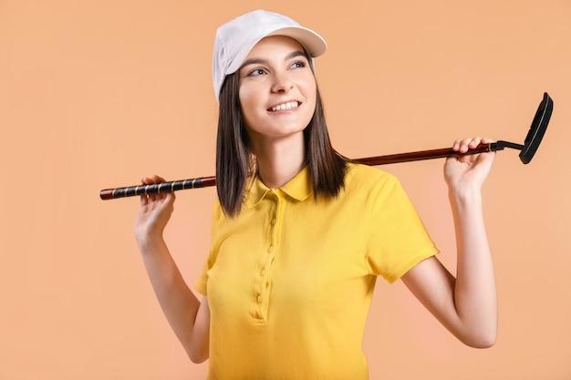 Mooie vrouwelijke golfer op kleur achtergrond