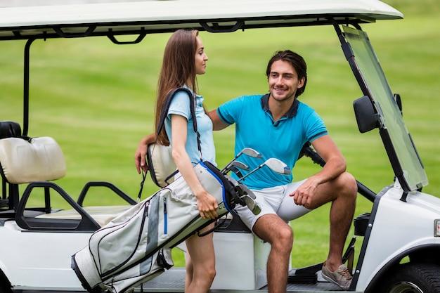 Mooie vrouwelijke golfspeler die een golfzak draagt