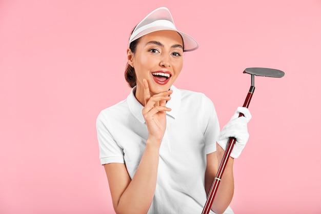 Mooie vrouwelijke golfspeler op gekleurde achtergrond