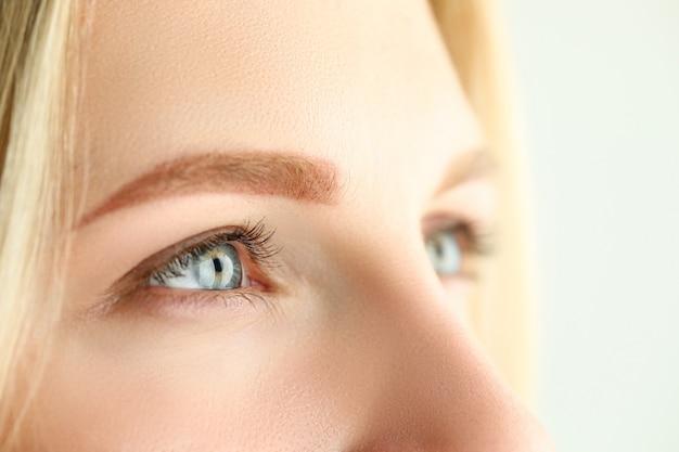 Mooie vrouwelijke groen en grijs gekleurde ogen die ergens afstandsclose-up onderzoeken