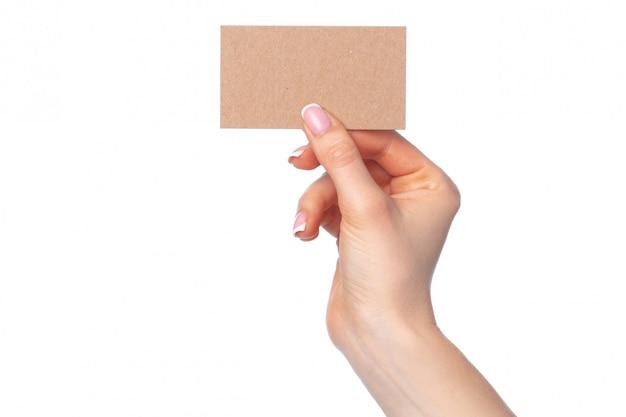 Mooie vrouwelijke hand die wit adreskaartje op wit houdt
