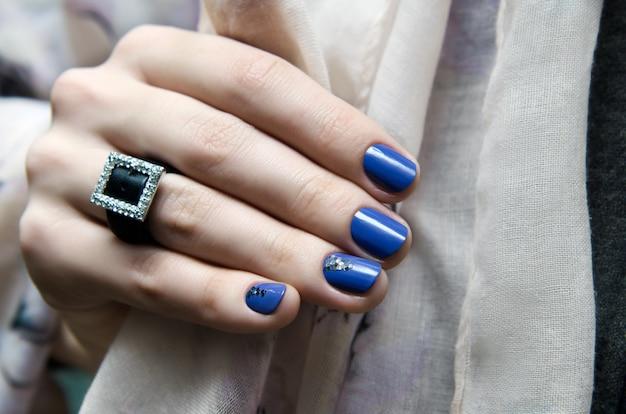 Mooie vrouwelijke hand met blauw nagelontwerp.