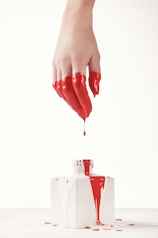 Mooie vrouwelijke hand, met haar vloeiende witte en rode verf, witte achtergrond. nagel verlenging. manicure, kuuroordsalon. creatief, reclame. kom tot rust.
