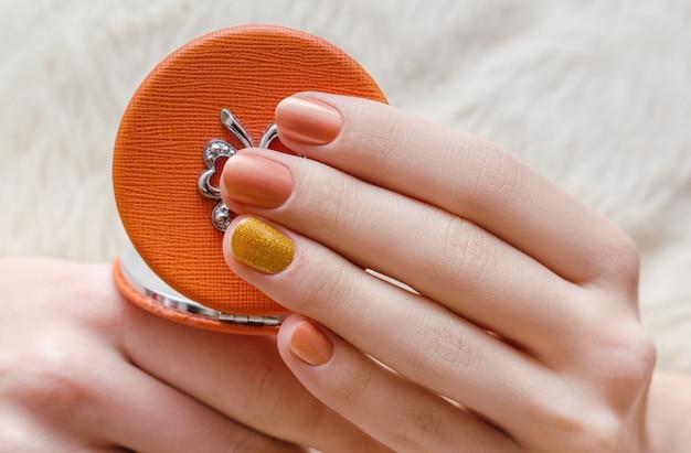 Mooie vrouwelijke hand met oranje nagelontwerp.