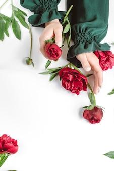 Mooie vrouwelijke hand met rode bloemen op wit