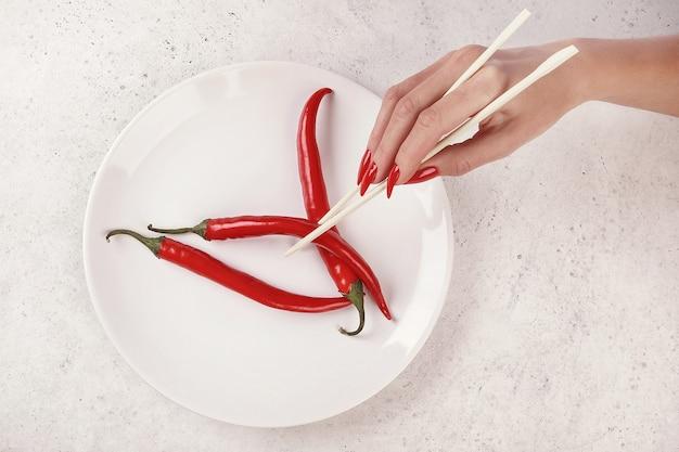 Mooie vrouwelijke hand met rode manicure, witte achtergrond, chinese stokken die rode hete peper houden. nagel verlenging. manicure, kuuroordsalon.