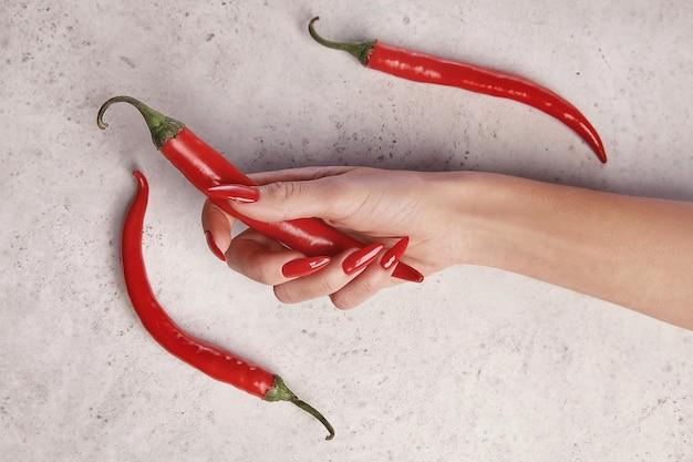 Mooie vrouwelijke hand met rode manicure, witte achtergrond, met rode peper. nagel verlenging. manicure, kuuroordsalon.