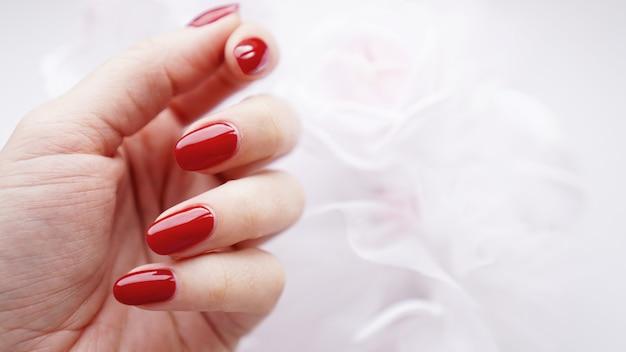 Mooie vrouwelijke hand met rode nagels tegen de achtergrond van een wit huwelijksboeket