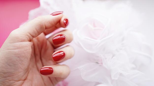 Mooie vrouwelijke hand met rode nagels tegen het oppervlak van een wit huwelijksboeket