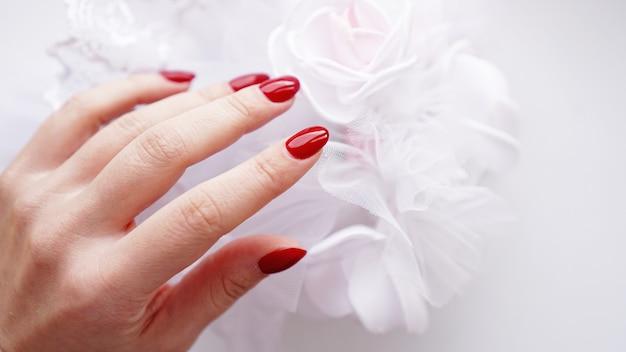 Mooie vrouwelijke hand met rode spijkers tegen van een wit huwelijksboeket