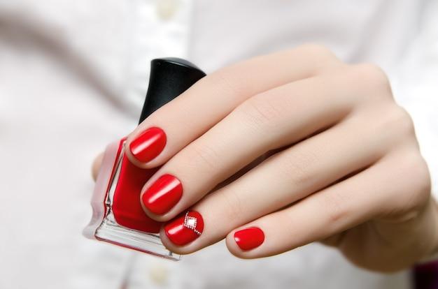 Mooie vrouwelijke hand met rood nagelontwerp.