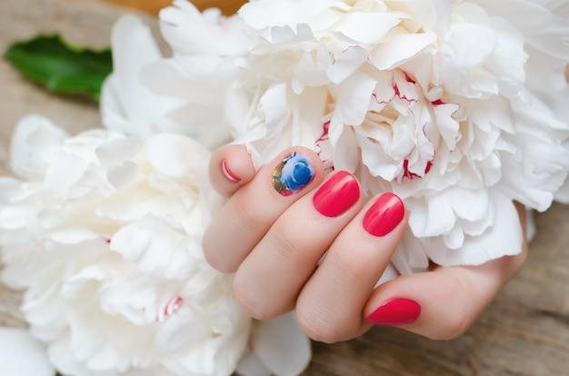 Mooie vrouwelijke hand met rood nagelontwerp