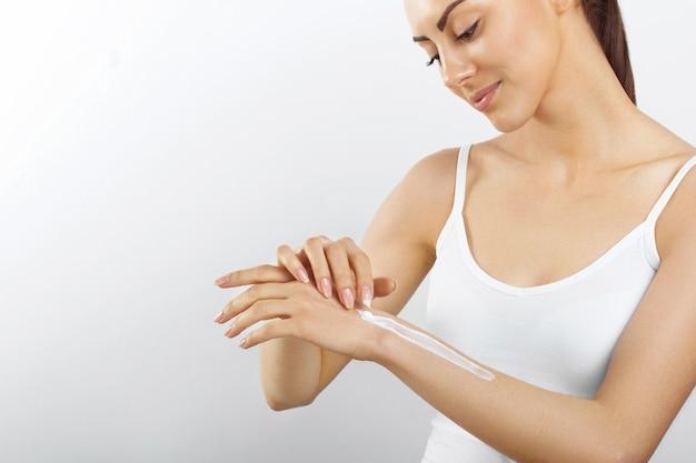Mooie vrouwelijke hand met witte room