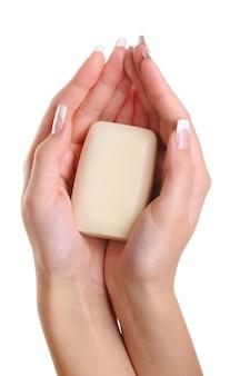Mooie vrouwelijke handen houden de witte zeep vast