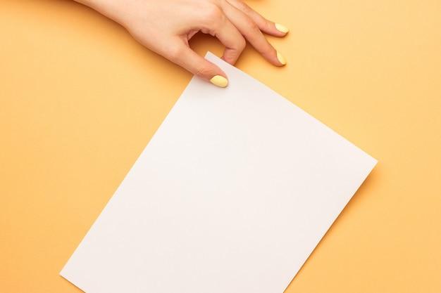 Mooie vrouwelijke handen houden lege a4-formulier op geel