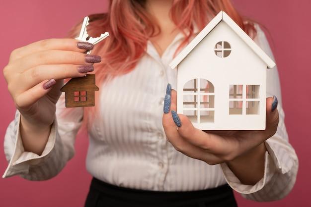 Mooie vrouwelijke handen houden sleutels vast en een huis op de achtergrond