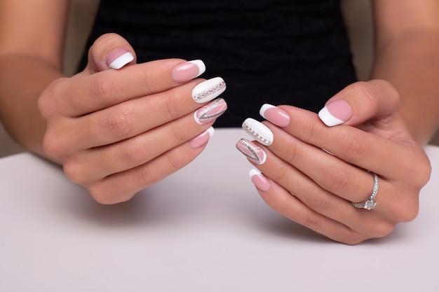 Mooie vrouwelijke handen met bruiloft manicure nagels met ring op witte achtergrond