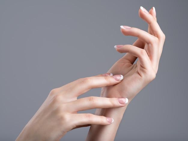 Mooie vrouwelijke handen met franse manicure op nagels
