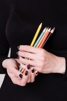 Mooie vrouwelijke handen met kleurpotloden op zwart