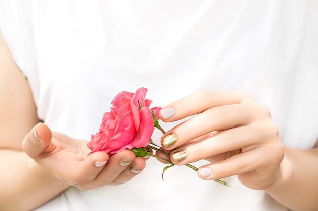 Mooie vrouwelijke handen met perfect gouden en roze nagelontwerp houden verse roze bloem