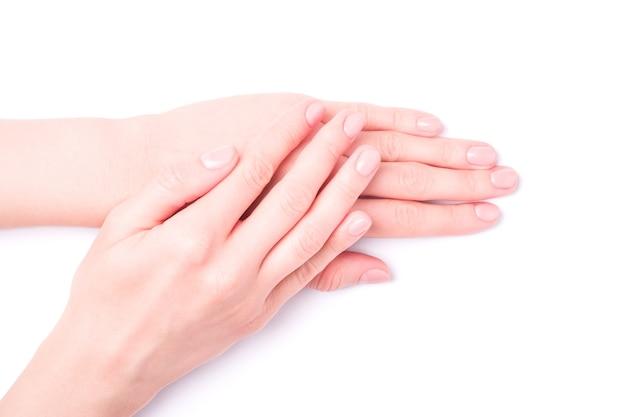 Mooie vrouwelijke handen met verse schattige manicure, huid en nagel zorg concept, geïsoleerd