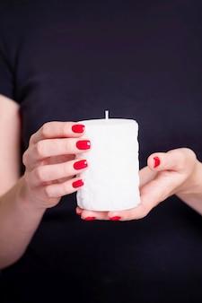 Mooie vrouwelijke handen met witte kaars. manicure met rode nagellak.