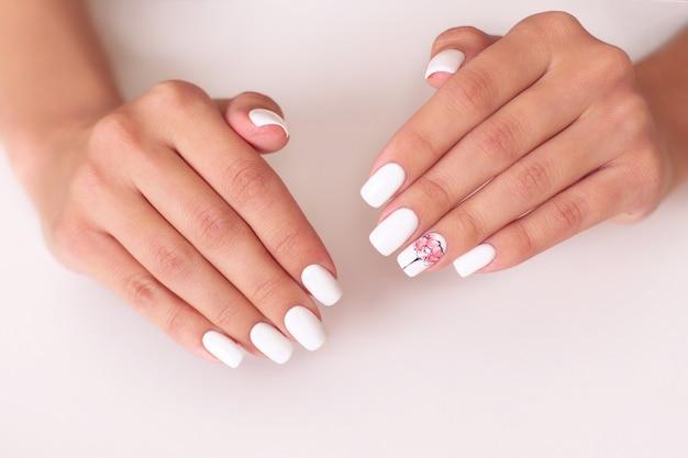 Mooie vrouwelijke handen met witte manicure nagels, pioenrozen ontwerp