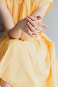 Mooie vrouwelijke handen op een gele achtergrond. zorg goed voor je hand. fijne handpalm met natuurlijke manicure, schone huid. lichtroze nagels