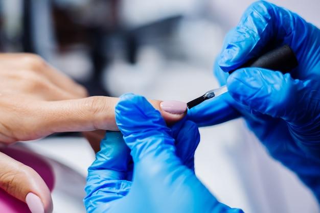 Mooie vrouwelijke handen vingernagel behandeling maken proces professionele nagelvijl boor in actie schoonheid en handverzorging concept
