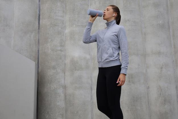 Mooie vrouwelijke hardloper die buiten staat, drinkwater uit de fles. fitness vrouw neemt een pauze na het uitvoeren van een training.