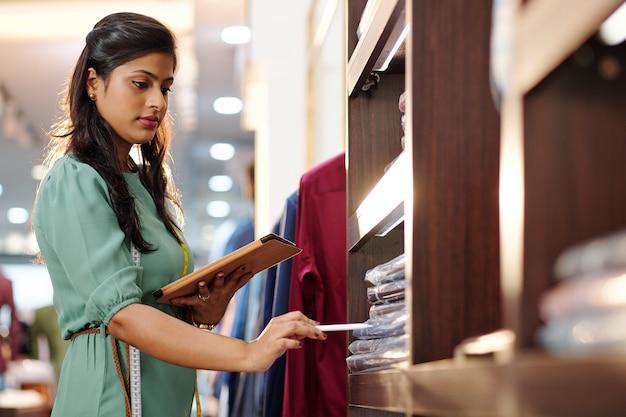 Mooie vrouwelijke indiase kleermaker die verpakte voltooide bestellingen op de plank telt en online document vult