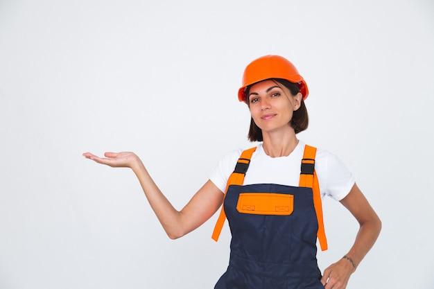Mooie vrouwelijke ingenieur bij het bouwen van een beschermende helm op een witte zelfverzekerde glimlach houdt lege ruimte aan de linkerhand vast