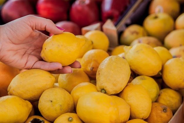 Mooie vrouwelijke klant die citroenen koopt op fruitmarkt. vrouw kiezen citroenen. vrouw kiezen verse citroenen voor het meten in de supermarkt
