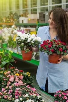 Mooie vrouwelijke klant ruiken kleurrijke bloeiende bloempotten in de winkel. tuinieren in serre. botanische tuin, bloementeelt, tuinbouwconcept