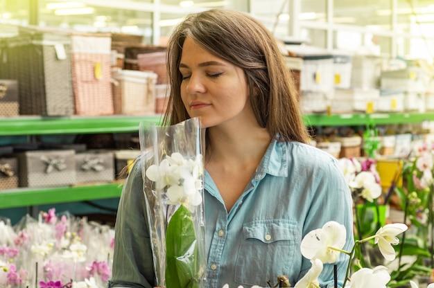 Mooie vrouwelijke klant ruiken kleurrijke bloeiende orchideeën in de winkel. tuinieren in serre. botanische tuin, bloementeelt, tuinbouwconcept