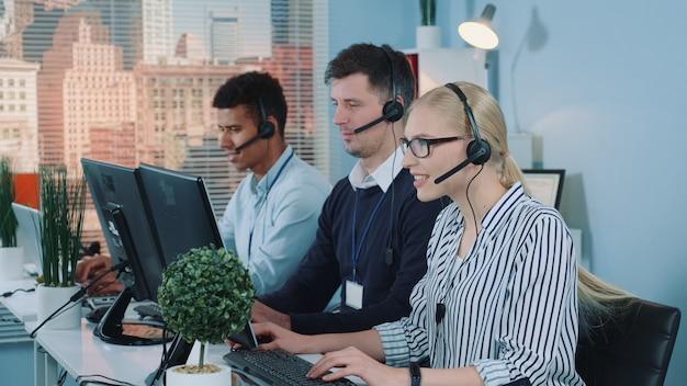Mooie vrouwelijke klantenservice die in druk callcenter werkt door met de internationale cliënt te spreken